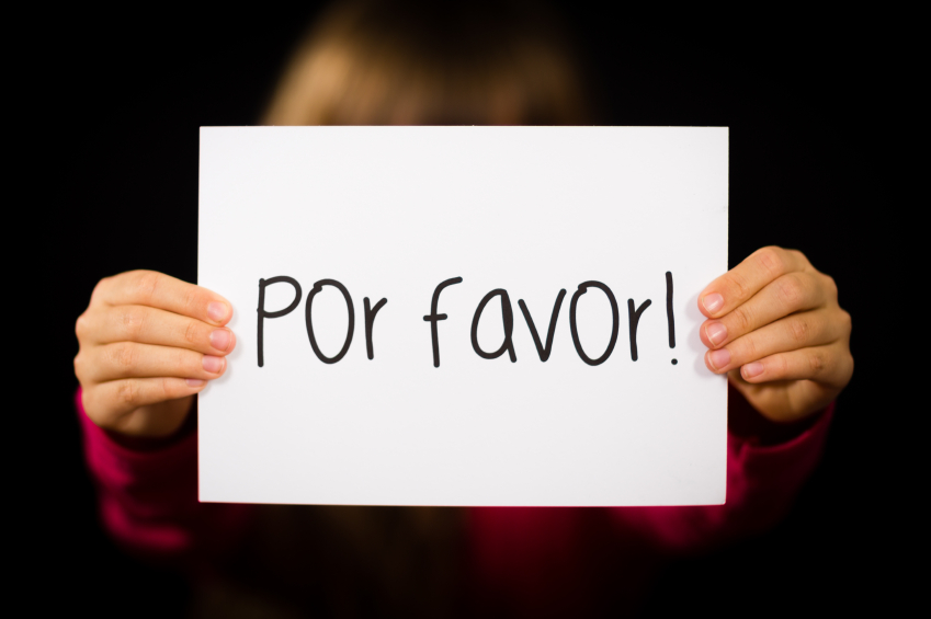 Studio shot of child holding a sign with Spanish words Por Favor - Please