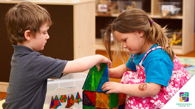 two kids play with colorful magnetic building blocks
