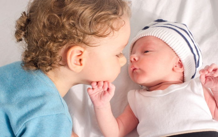 Big brother kissing his little sibling.