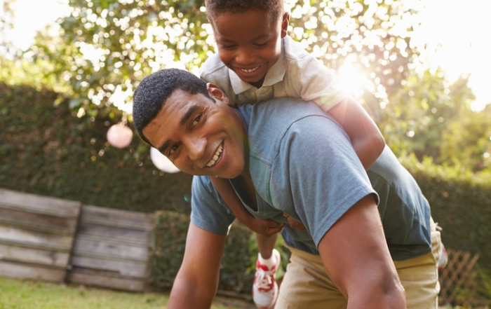 Young black boy playing on dad's back in a garden