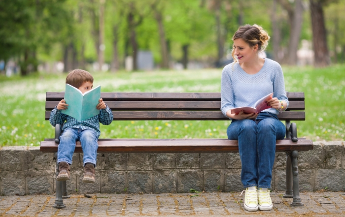 Woman and Boy Reading Books in a Park