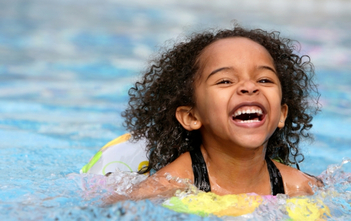 A jubilant kid swimming in a pool