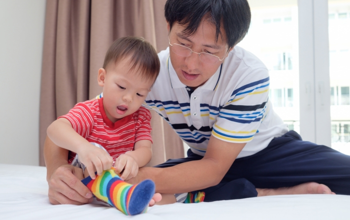 Asian father teaching cute little Asian 2 years old toddler boy child putting on his own socks, Dad and son sitting on bed concentrate on wearing socks