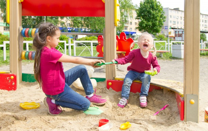 Conflict on the playground. Two sisters fighting over a toy in the sandbox. Kid sister crying all throat