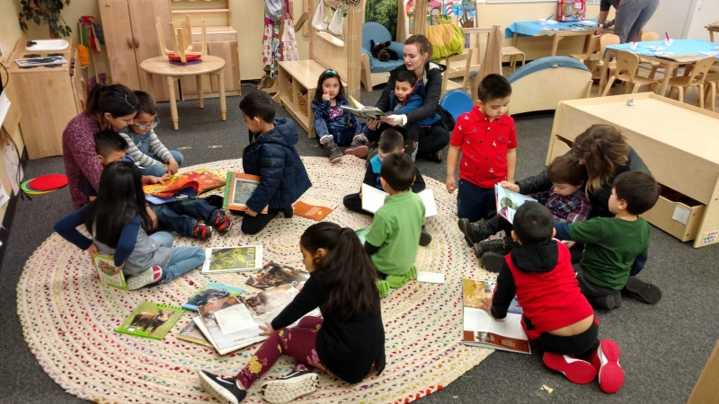 group of preschoolers and teachers reading books at circle mat