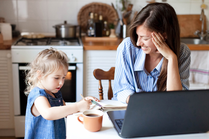 Mother working at home on laptop in the kitchen smiling at young daughter who is drawing in a notebook on the table.