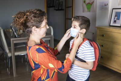 A smiling mother is kneeling down in her home putting a surgical mask on her young son's face who is wearing a backpack..
