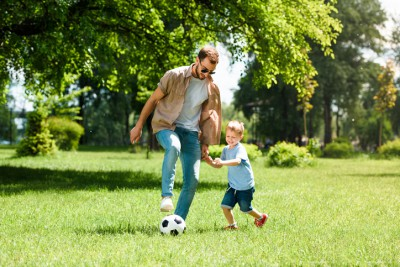 Dad and his young son are playing soccer on green grass on a sunny summer day